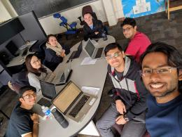 a group of students with laptop computers smiling at camera