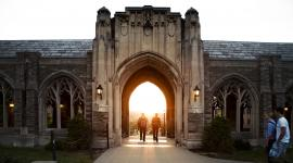 two students walking on Cornell campus into the sunset